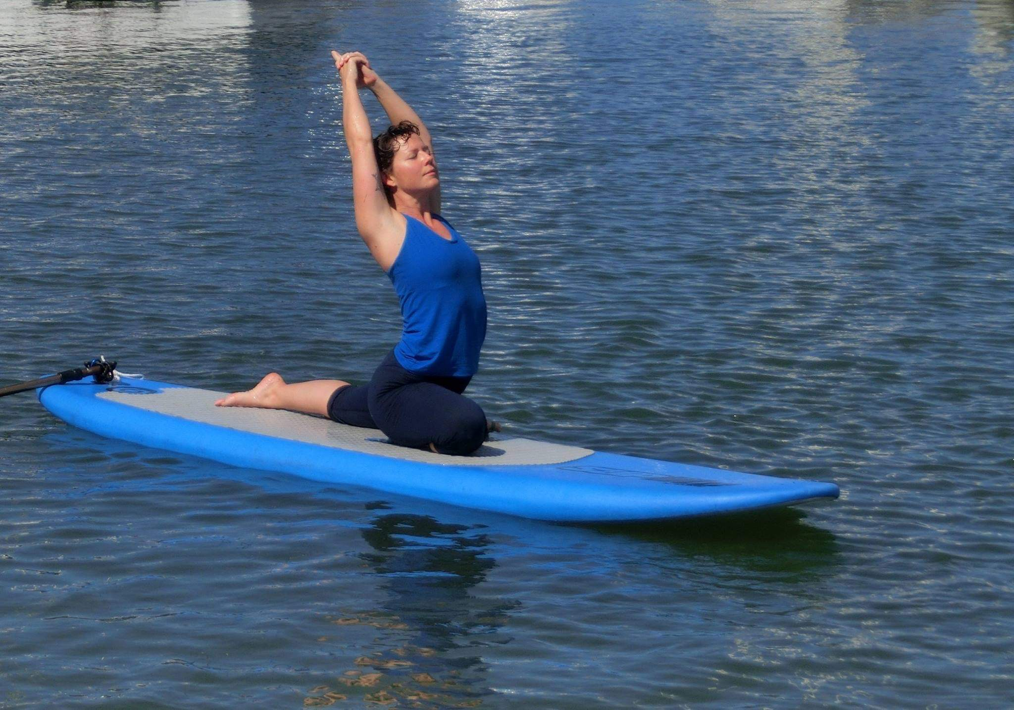 Lisa in Pigeon Pose on a SUP board.